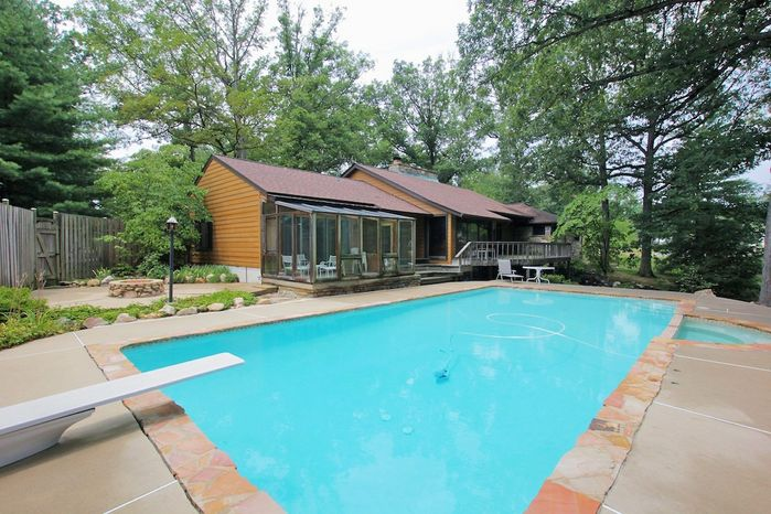 The backyard features a swimming pool with a diving board, whirlpool tub and stone decks.