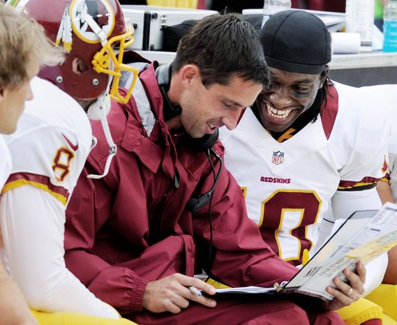 Something strikes Robert Griffin III as funny during a strategy session with offensive coordinator Kyle Shanahan during a preseason game against the Colts. Shanahan, shown with Griffin during drills below, says it will be important to take pressure off the rookie by running the ball effectively. (Preston Keres/Special to The Washington Times)
