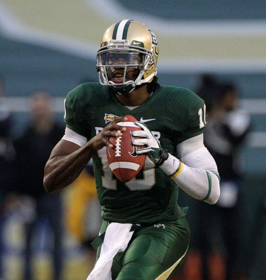 Baylor quarterback Robert Griffin III prepares to pass in the second half of an NCAA college football game against Texas Saturday, Dec. 3, 2011, in Waco, Texas. Griffin III ran for two touchdowns and passed for two more to lead No. 19 Baylor to a 48-24 win over Texas. (AP Photo/Tony Gutierrez)