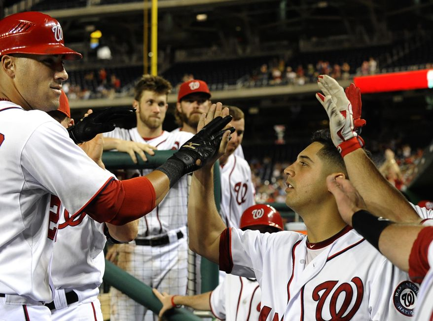 Washington Nationals pitcher Gio Gonzalez, lower right, congratulates teammate Ian Desmond after Desmond's seventh-inning home run gave the Nationals a 7-0 lead over the Chicago Cubs during their baseball game at Nationals Park, Wednesday, Sept. 5, 2012, in Washington. The Nationals defeated the Cubs 9-1 and Gio Gonzalez won his 18th game of the season. (AP Photo/Richard Lipski)