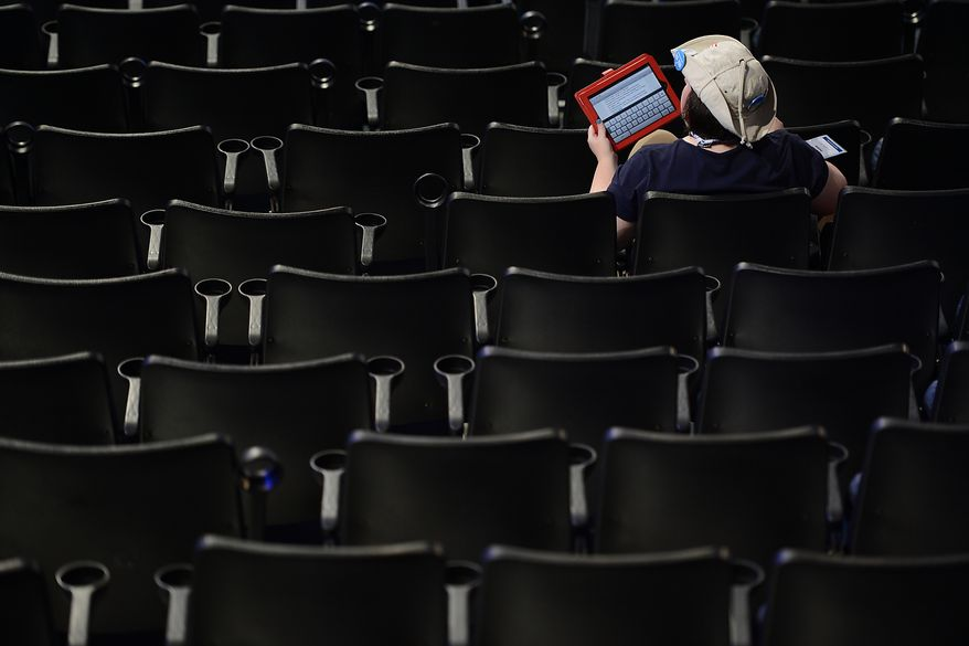 Washington delegate Jennifer Sutton, of Iffaquah, Wash., blogs from the delegates' seats before the start of the second day of the Democratic National Convention at the Time Warner Arena in Charlotte, N.C., on Wednesday, September 5, 2012.  (Barbara Salisbury/ The Washington Times)