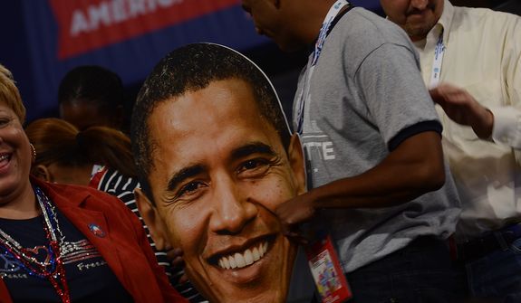 A delegate holds a face of President Obama on the night he accepts his party's nomination for a second term at the Democratic National Convention in the Time Warner Arena in Charlotte, N.C., on Sept. 6, 2012. (Barbara Salisbury/The Washington Times)