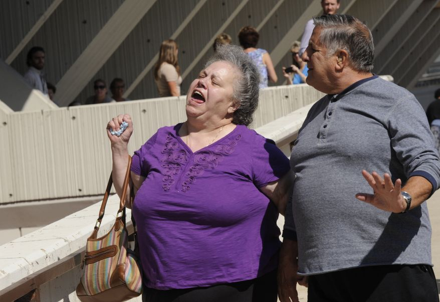 Hank and Marcia Savio, father and stepmother of Kathleen Savio, celebrate Sept. 6, 2012, outside the Will County Courthouse after word spreads that former Bolingbrook police officer Drew Peterson was found guilty of murdering his third wife Kathleen Savio Thursday,  in Joliet, Ill. (Associated Press)