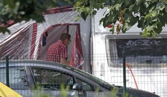 An investigator enters the trailer where the slain British family were holidaying in a camp site of Saint Jorioz, near Annecy, France, Thursday, Sept. 6, 2012. A 4-year-old British girl hid for eight hours beneath the bodies of slain family members in the back of their car in a nearby forest, before she was discovered by French investigators who had been guarding the vehicle, a prosecutor said Thursday. (AP Photo/Lionel Cironneau)