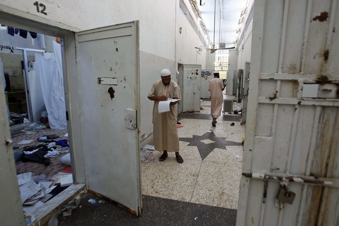 Libyans search for documents inside Abu Salim Prison, Libya's most notorious prison during Col. Moammar Gadhafi's regime and the scene of a 1996 massacre of prisoners, in Tripoli, Libya, on Saturday, Aug. 27, 2011. (AP Photo/Francois Mori)