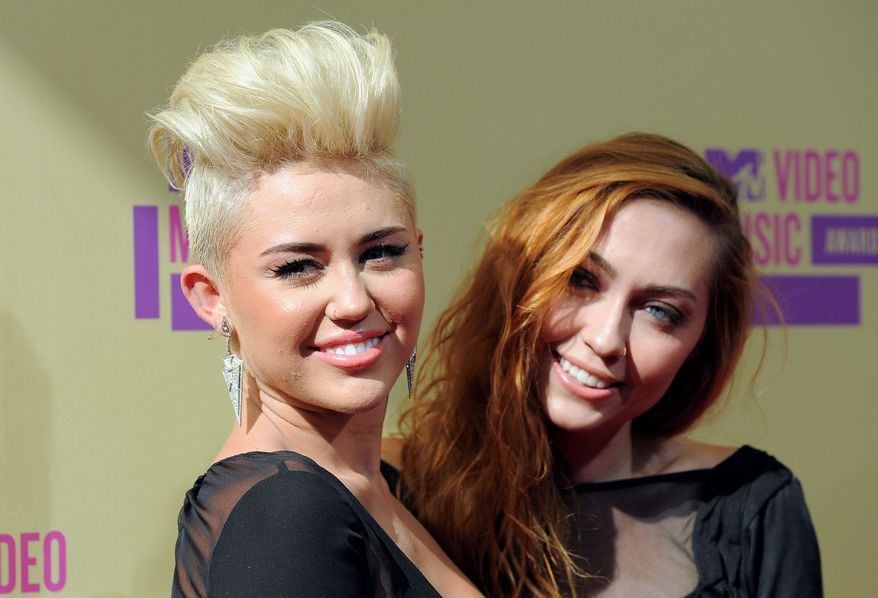 Miley Cyrus and her sister Brandi Cyrus attend the MTV Video Music Awards on Thursday, Sept. 6, 2012, in Los Angeles. (Photo by Jordan Strauss/Invision/AP)