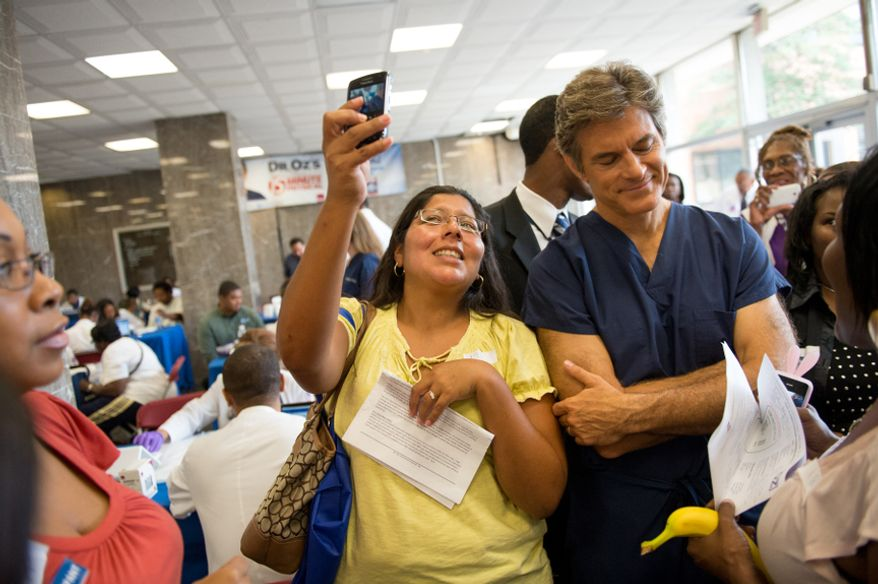 Amy Ramirez of Kensington, Md., left, leans in to get a photo with Dr. Mehmet Oz, host of The Dr. Oz Show as he hosts a 15-minute clinic open to the public with the help of Howard University medical students to get a very basic idea of people's general risk for heart disease and diabetes at Howard University in the District on Wednesday, Sept. 5, 2012. (Andrew Harnik/The Washington Times)