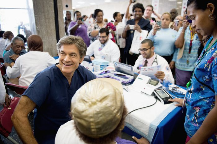 """**FILE** Dr. Mehmet Oz, host of """"The Dr. Oz Show,"""" sits down to go through the exam of Gladys Nealy of Washington, D.C., during a 15-minute clinic open to the public with the help of Howard University medical students at the school's campus on Sept. 5, 2012. The clinic was held to get a basic idea of people's general risk for heart disease and diabetes. (Andrew Harnik/The Washington Times)"""
