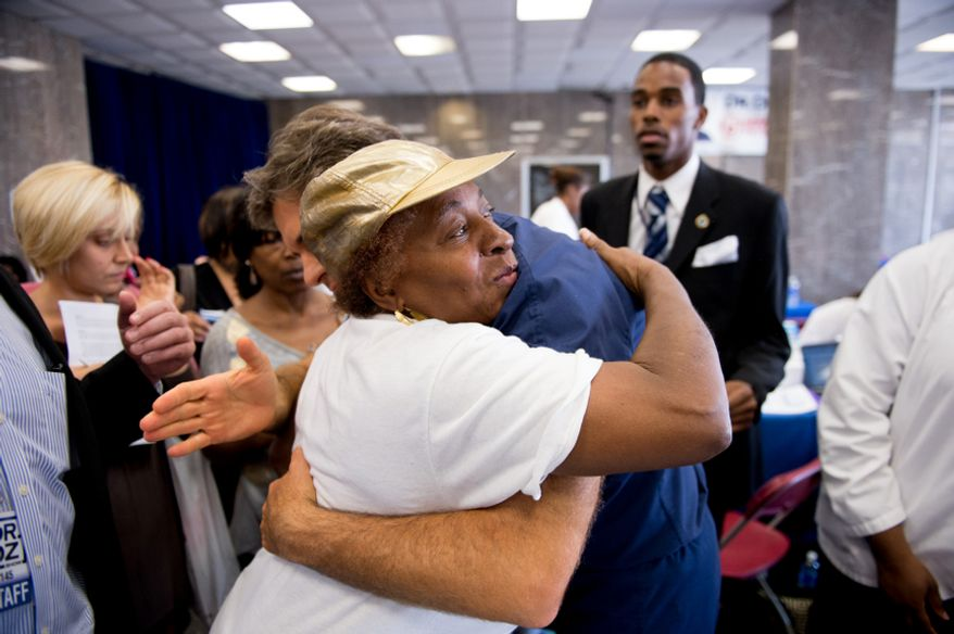 Dr. Mehmet Oz, host of The Dr. Oz Show gets a hug from Gladys Nealy of Washington, D.C. after going through her exam with her during a 15-minute clinic open to the public with the help of Howard University medical students to get a very basic idea of people's general risk for heart disease and diabetes at Howard University in the District on Wednesday, Sept. 5, 2012.