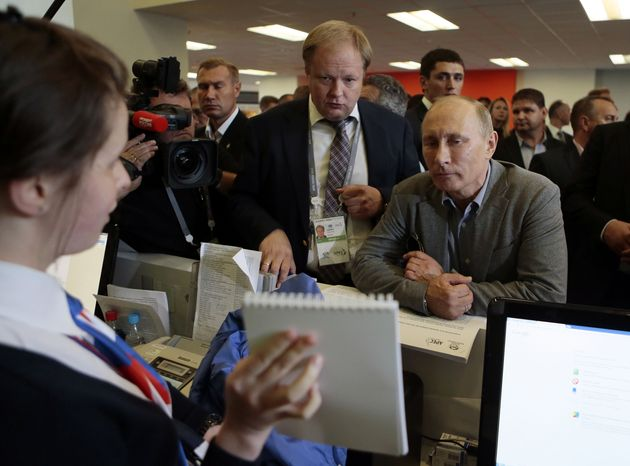 Russian President Vladimir Putin (right) is shown the contents of a media kit during a visit to the media center for the Asia-Pacific Economic Cooperation summit in Vladivostok, Russia, on Thursday, Sept. 6, 2012. (AP Photo/Mikhail Metzel)