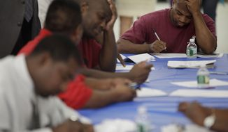 Job seekers fill out applications at a construction job fair in New York on Tuesday, Aug. 21, 2012. (AP Photo/Seth Wenig)