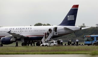 ** FILE ** Passengers deplane from a US Airways jet at Philadelphia International Airport after the aircraft returned to the field on Thursday, Sept. 6, 2012, following a tip to authorities that an explosive liquid was on board. (AP Photo/Matt Rourke)