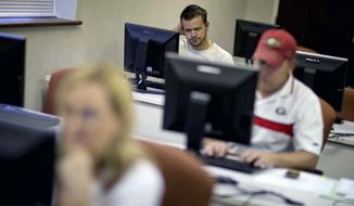 In this Aug. 22, 2012, file photo, Scott Marshall, top, of Calhoun, Ga., files for unemployment, in Dalton, Ga. (AP Photo/David Goldman, File)