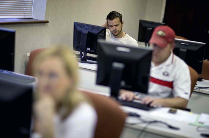 In this Aug. 22, 2012, file photo, Scott Marshall, top, of Calhoun, Ga., files for unemployment, in Dalton, Ga. (AP Photo/David Goldman, File)