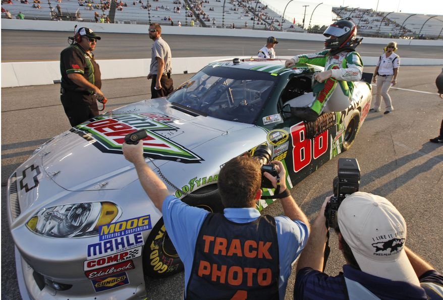 Dale Earnhardt Jr. gets out of his car after winning the pole during qualifying for the NASCAR Sprint Cup Series auto race at Richmond International Raceway in Richmond, Va., Friday, Sept. 7, 2012. (AP Photo/Steve Helber)