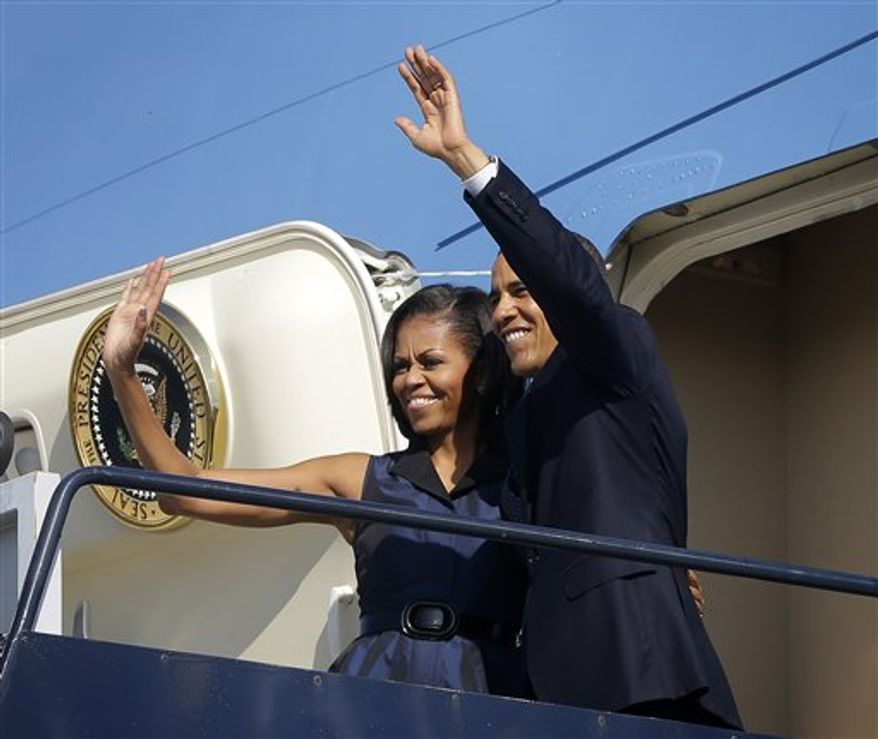 President Obama and first lady Michelle Obama wave Sept. 7, 2012, as they board Air Force One before their departure from Charlotte International Airport in Charlotte, N.C. (Associated Press)