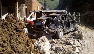 In this photo provided by China's Xinhua News Agency, damaged cars are seen in Luozehe town, Yiliang County, southwest China's Yunnan Province, Friday, Sept. 7, 2012. A series of earthquakes collapsed houses and triggered landslides in a remote mountainous part of southwestern China on Friday, killing dozens of people with the toll expected to rise. (AP Photo/Xinhua, Zhou Hongpeng)