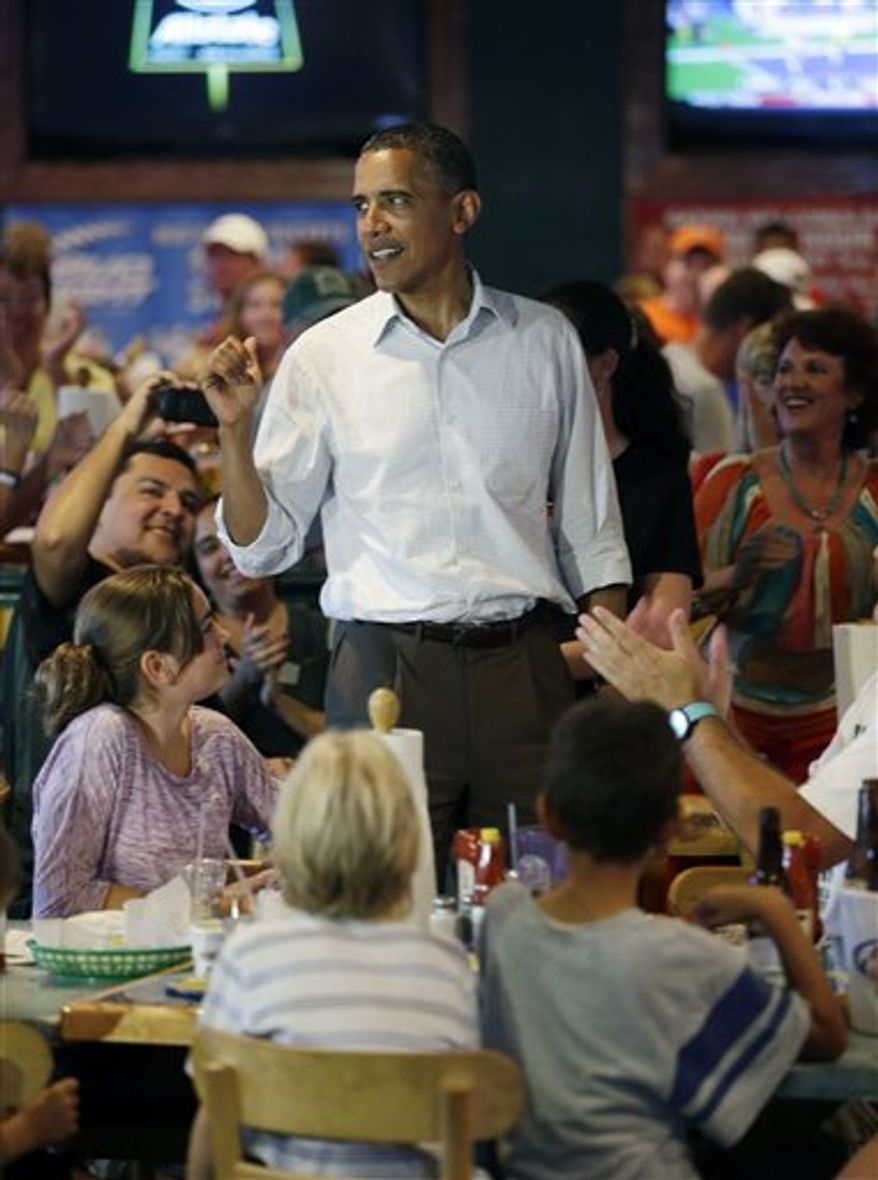 President Obama greets patrons Sept. 8, 2012, during an unscheduled stop at Gator's Dockside in Orlando, Fla. (Associated Press)