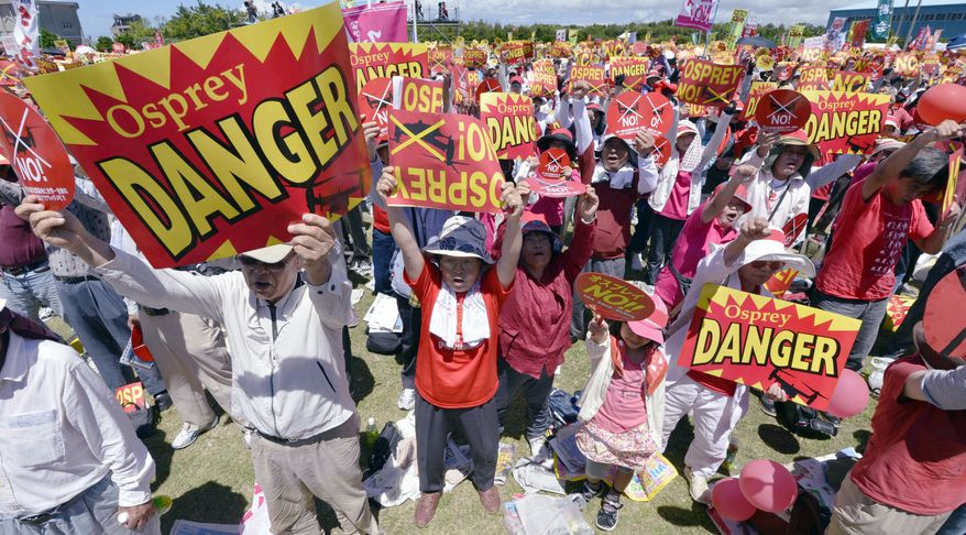 Japanese protesters raise signs Sunday at a seaside park on Okinawa to oppose U.S. plans to deploy 12 MV-22 Osprey aircraft on the island. Safety concerns boiled over after Osprey crashes in Morocco and Florida earlier this year. (Associated Press)