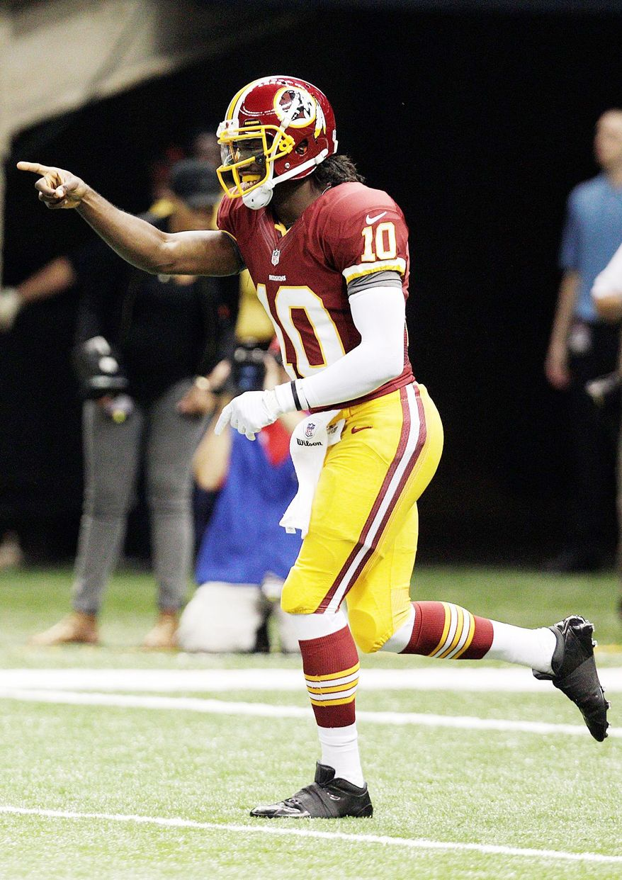 Redskins quarterback Robert Griffin III had plenty of reason to celebrate at he went 19 of 26 for 320 yards and two touchdowns in his NFL debut Sunday.  (Associated Press)