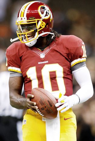 Washington Redskins quarterback Robert Griffin III (10) warms up before an NFL football game against the New Orleans Saints at the Mercedes-Benz Superdome in New Orleans, Sunday, Sept. 9, 2012. (AP Photo/Bill Haber)