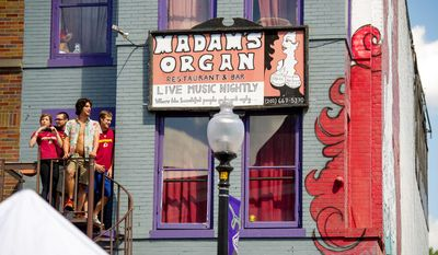 Redskins fans take a look at the street from the second floor of Madame's Organ bar. (Andrew Harnik/The Washington Times)