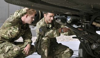 Britain's Prince Harry (left) examines the 30mm cannon of an Apache attack helicopter with an unidentified member of his squadron on Friday, Sept. 7, 2012, at Camp Bastion in Afghanistan, where he will be a co-pilot gunner. The 27-year-old prince, known as Capt. Harry Wales, is on his second tour of duty in Afghanistan. (AP Photo/John Stillwell, Pool)