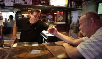 Dustin Croick (left), owner of the King Eddy Saloon, gives a hand to patron Bob Wardsworth, 66, on Thursday, Aug. 16, 2012, in Los Angeles. (AP Photo/Damian Dovarganes)