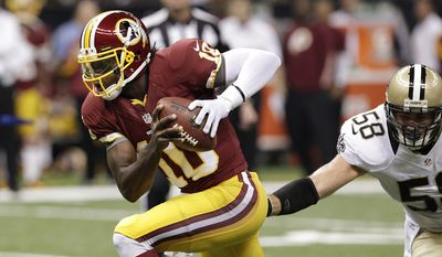 Washington Redskins quarterback Robert Griffin III (10) tries to elude New Orleans Saints linebacker Scott Shanle (58) in the first half of an NFL football game at the Mercedes-Benz Superdome in New Orleans, Sunday, Sept. 9, 2012. (AP Photo/Matthew Hinton)