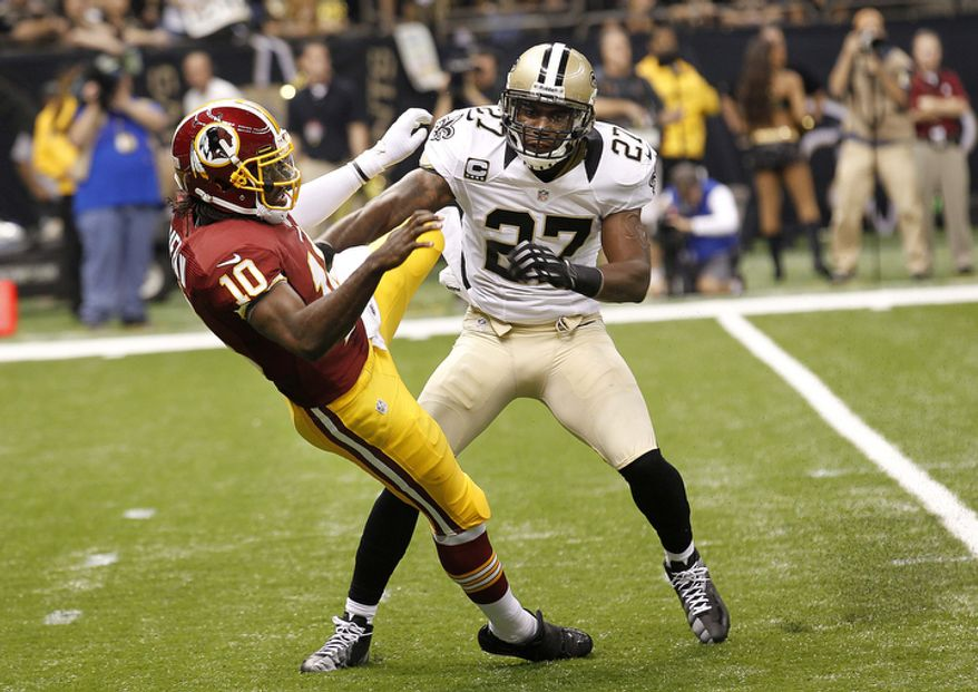 Washington Redskins quarterback Robert Griffin III (10) is hit by New Orleans Saints free safety Malcolm Jenkins (27) after after releasing the ball on  touchdown pass in the first quarter of an NFL football game at the Mercedes-Benz Superdome in New Orleans, Sunday, Sept. 9, 2012. (AP Photo/Bill Haber)