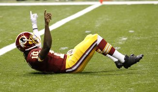 Washington Redskins quarterback Robert Griffin III (10) reacts after throwing a touchdown pass in the first quarter of an NFL football game against the New Orleans Saints at Mercedes-Benz Superdome in New Orleans, Sunday, Sept. 9, 2012. (AP Photo/Bill Haber)