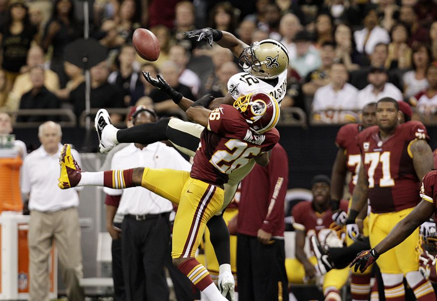 New Orleans Saints wide receiver Marques Colston (12) and Washington Redskins cornerback Josh Wilson (26) in the second half of an NFL football game at the Mercedes-Benz Superdome in New Orleans, Sunday, Sept. 9, 2012. (AP Photo/Matthew Hinton)