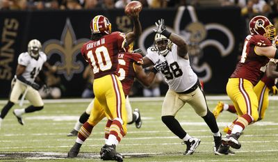 Washington Redskins quarterback Robert Griffin III (10) passes as New Orleans Saints defensive tackle Sedrick Ellis (98) rushes in the second half of an NFL football game at the Mercedes-Benz Superdome in New Orleans, Sunday, Sept. 9, 2012. (AP Photo/Bill Haber)