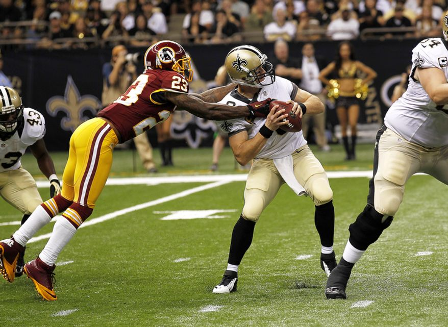 New Orleans Saints quarterback Drew Brees (9) is sacked by Washington Redskins cornerback DeAngelo Hall (23) in the first half of an NFL football game at the Mercedes-Benz Superdome in New Orleans, Sunday, Sept. 9, 2012. (AP Photo/Bill Haber)