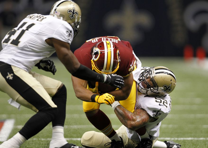 Washington Redskins running back Roy Helu (29)is tackled by New Orleans Saints linebacker Jonathan Casillas (52) and strong safety Roman Harper (41) in the first half of an NFL football game at the Mercedes-Benz Superdome in New Orleans, Sunday, Sept. 9, 2012. (AP Photo/Gerald Herbert)
