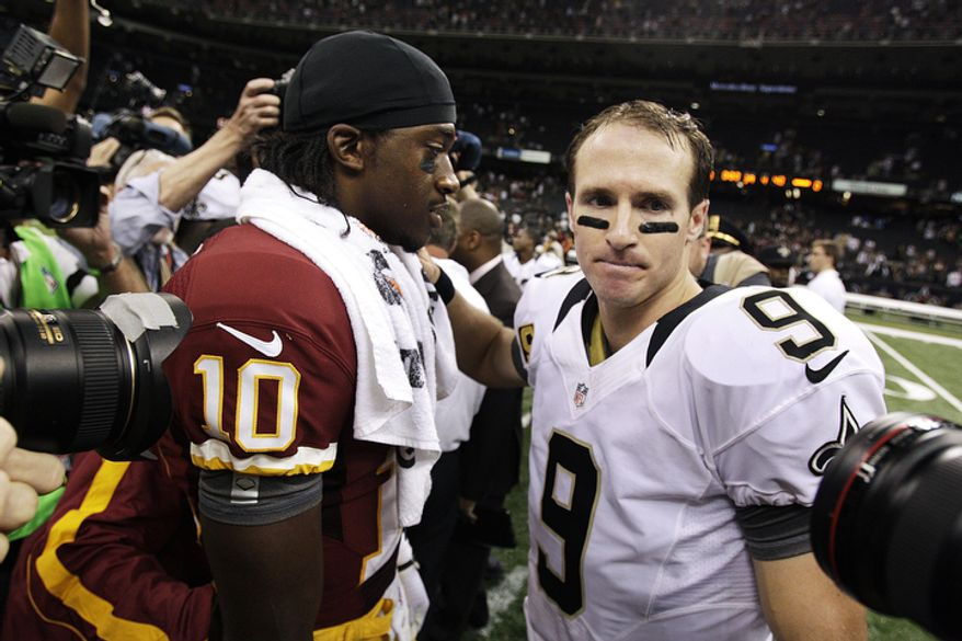 New Orleans Saints quarterback Drew Brees (9) greets Washington Redskins quarterback Robert Griffin III (10) after an NFL football game in New Orleans, Sunday, Sept. 9, 2012. The Redskins won 40-32. (AP Photo/Matthew Hinton)
