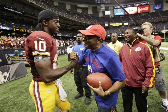 Washington Redskins quarterback Robert Griffin III (10) shakes hands with director Spike Lee after an NFL football game against the New Orleans Saints at the Mercedes-Benz Superdome in New Orleans, Sunday, Sept. 9, 2012. (AP Photo/Matthew Hinton)