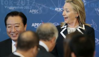 U.S. Secretary of State Hillary Rodham Clinton reacts as she meets fellow leaders for the group photo on the final day of the Asia-Pacific Economic Cooperation summit in Vladivostok, Russia, on Sunday, Sept. 9, 2012. (AP Photo/Mikhail Metzel)