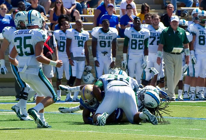 ** FILE ** In this photo provided by the University of Tulsa, Tulane's Devon Walker, bottom right, and Julius Warmsley (92) tackle Tulsa's Kenny Welcome, bottom left, during the first half of an NCAA college football game in Tulsa, Okla., Saturday, Sept. 8, 2012. (AP Photo/University of Tulsa, John Lew)