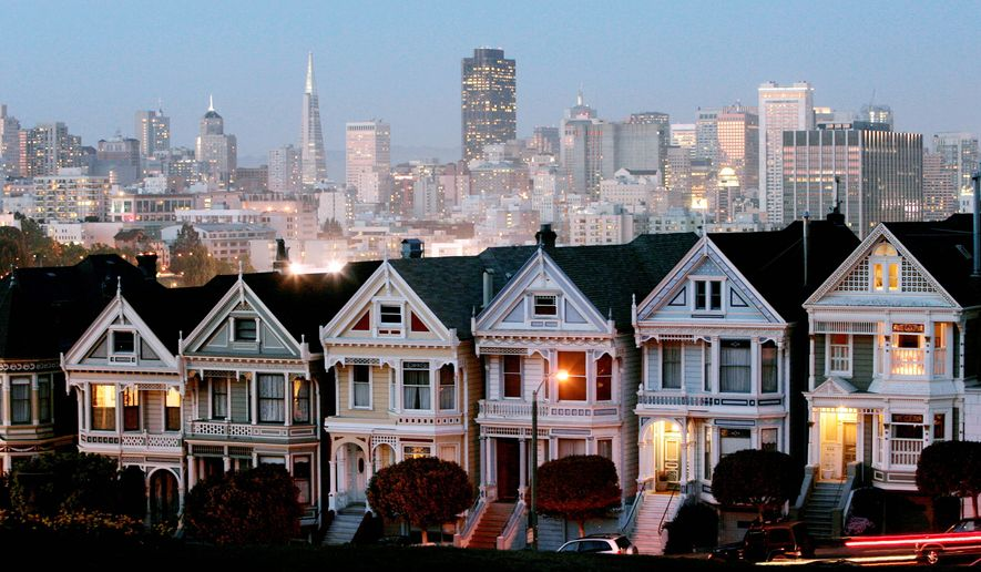 The San Francisco skyline rises behind a row of Victorian homes. (Associated Press)