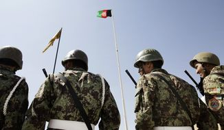 Afghan soldiers stand under their nation's flag as the U.S. turns over its prison at Bagram Airfield north of Kabul to the Afghan government. It holds about 3,000 inmates, raising fears that militants could be released and endanger U.S. troops. (Associated Press)