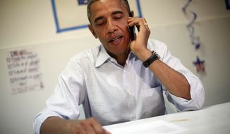 **FILE** President Obama uses a cell phone to contact supporters Sept. 9, 2012, during a surprise visit to a campaign office in Port St. Lucie, Fla. (Associated Press)