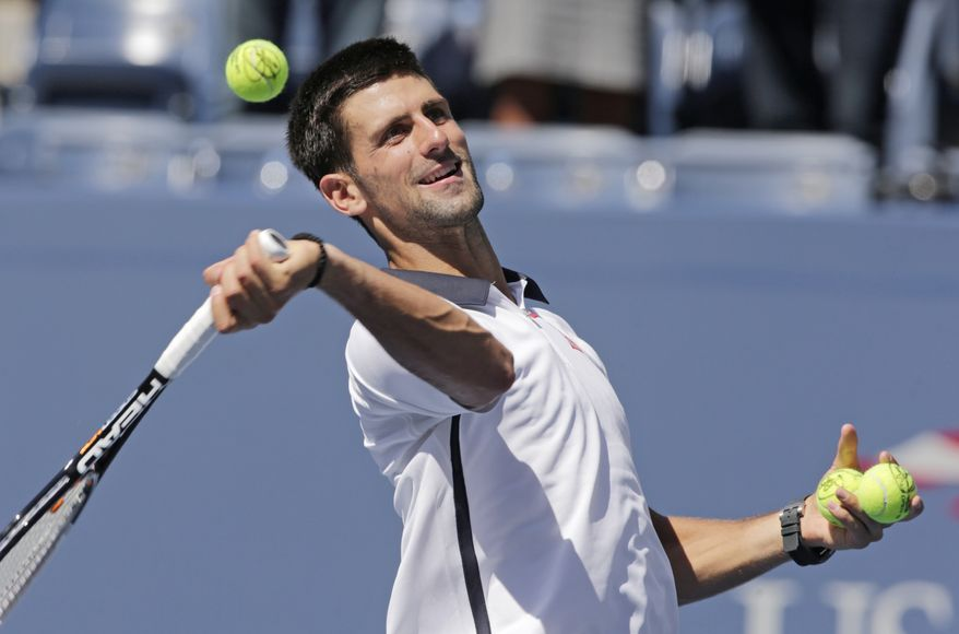 Serbia's Novak Djokovic hits balls into the stands after beating Spain's David Ferrer in a semifinal match at the 2012 US Open tennis tournament,  Sunday, Sept. 9, 2012, in New York. (AP Photo/Charles Krupa)