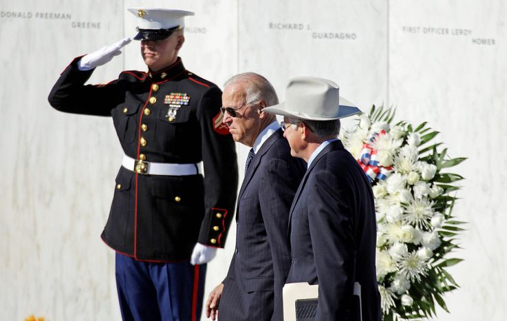 Vice President Joseph R. Biden (center) and Interior Secretary Kenneth L. Salazar arrive for a memorial service at the Flight 93 National Memorial in Shanksville, Pa., on Tuesday, passing the Wall of Names bearing the names of the 40 passengers and crew members aboard Flight 93 who died when it was hijacked and crashed on Sept. 11, 2001. (Associated Press)
