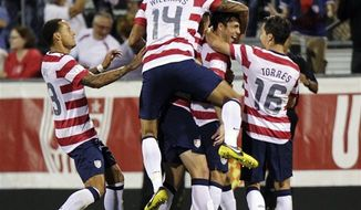 United States players celebrate a goal by Herculez Gomez against Jamaica during the second half of a World Cup qualifying soccer match, Tuesday, Sept. 11, 2012, in Columbus, Ohio. The United States won 1-0. (AP Photo/Jay LaPrete)