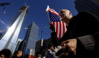 Marcio Rodriguez holds a United States flag as he pays his respects in front of the construction site of One World Trade Center on the 11th anniversary of the Sept. 11 terrorist attacks, Tuesday, Sept. 11, 2012, in New York. (AP Photo/Julio Cortez)