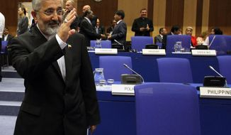 ** FILE ** Ali Asghar Soltanieh, Iran's ambassador to the International Atomic Energy Agency (IAEA), waves on Sept. 10, 2012, as he arrives for a meeting of the IAEA board of governors at the International Center in Vienna, Austria. (Associated Press)