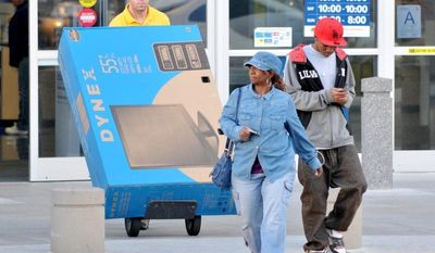 **FILE** Shoppers at a Best Buy in Victorville, Calif., leave the store March 30, 2012, as an employee walks a big-screen television to their car. (Associated Press/The Victor Valley Daily Press)