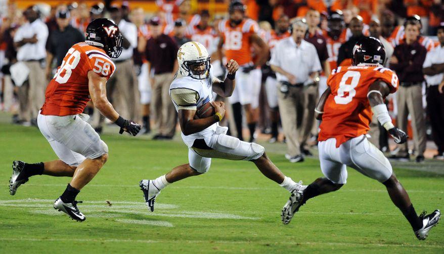 Virginia Tech linebacker Jack Tyler (58) and free safety Detrick Bonner (8) run down Georgia Tech quarterback Tevin Washington (13) during the second half of an NCAA college football game, Monday, Sept. 3, 2012, in Blacksburg, Va. Virginia Tech won 20-17 in overtime. (AP Photo/Don Petersen)