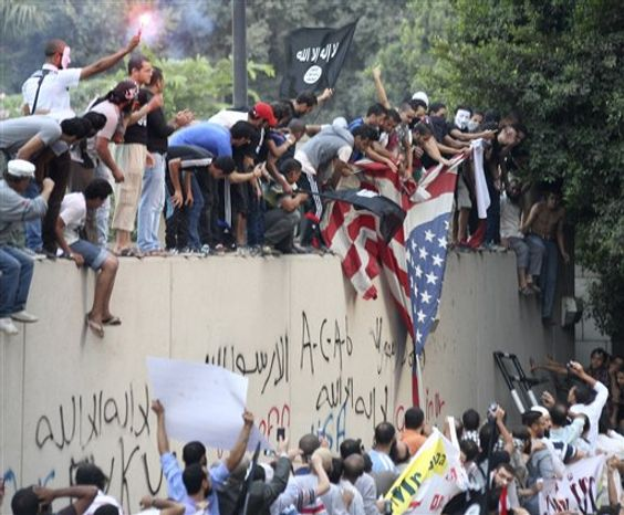 Protesters destroy an American flag pulled down from the U.S. embassy in Cairo, Egypt, Tuesday, Sept. 11, 2012. Egyptian protesters, largely ultra conservative Islamists, climbed the walls of the U.S. embassy in Cairo, went into the courtyard and brought down the flag, replacing it with a black flag with Islamic inscription, in protest of a film deemed offensive of Islam. (AP Photo/Mohammed Abu Zaid)